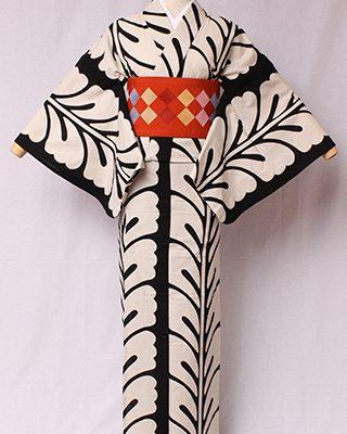 古典文様を反物巾一杯に配し、大胆でモダンにしたシリーズ。歌舞伎の「藤娘」で用いられる文様。連なって咲く花の様から縁起物。絽素材使用。