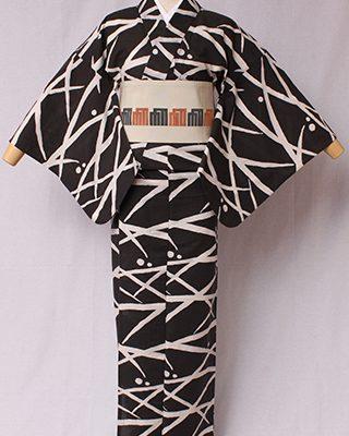 古典文様を反物巾一杯に配し、大胆でモダンにしたシリーズ。草木と露をデザイン化した古典文様。日本独特の情緒のあるモチーフ。絽素材使用。