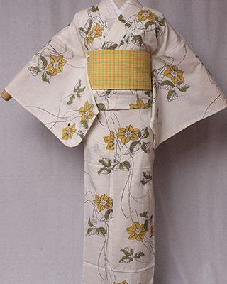 織り模様に格子柄が浮き上がる綿紅梅クラシックな生地を使用し、手捺染で染めています。白地に黄色い花柄はどこか懐かさを感じさせる仕上がり。
