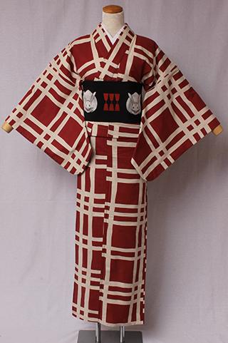古典文様を反物巾一杯に配し、大胆でモダンにしたシリーズ。格子は縞と並んで粋な柄の代表。金子画伯が愛用した着物も多くが格子。絽素材使用。