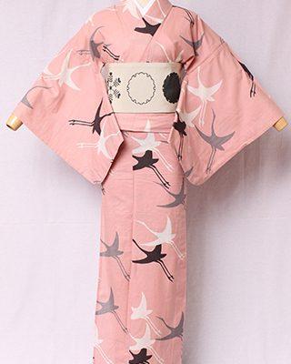 古典文様を反物巾一杯に配し、大胆でモダンにしたシリーズ。何羽もの鶴が飛び交う姿をデザイン化した文様を古く「千羽鶴」という。絽素材使用。